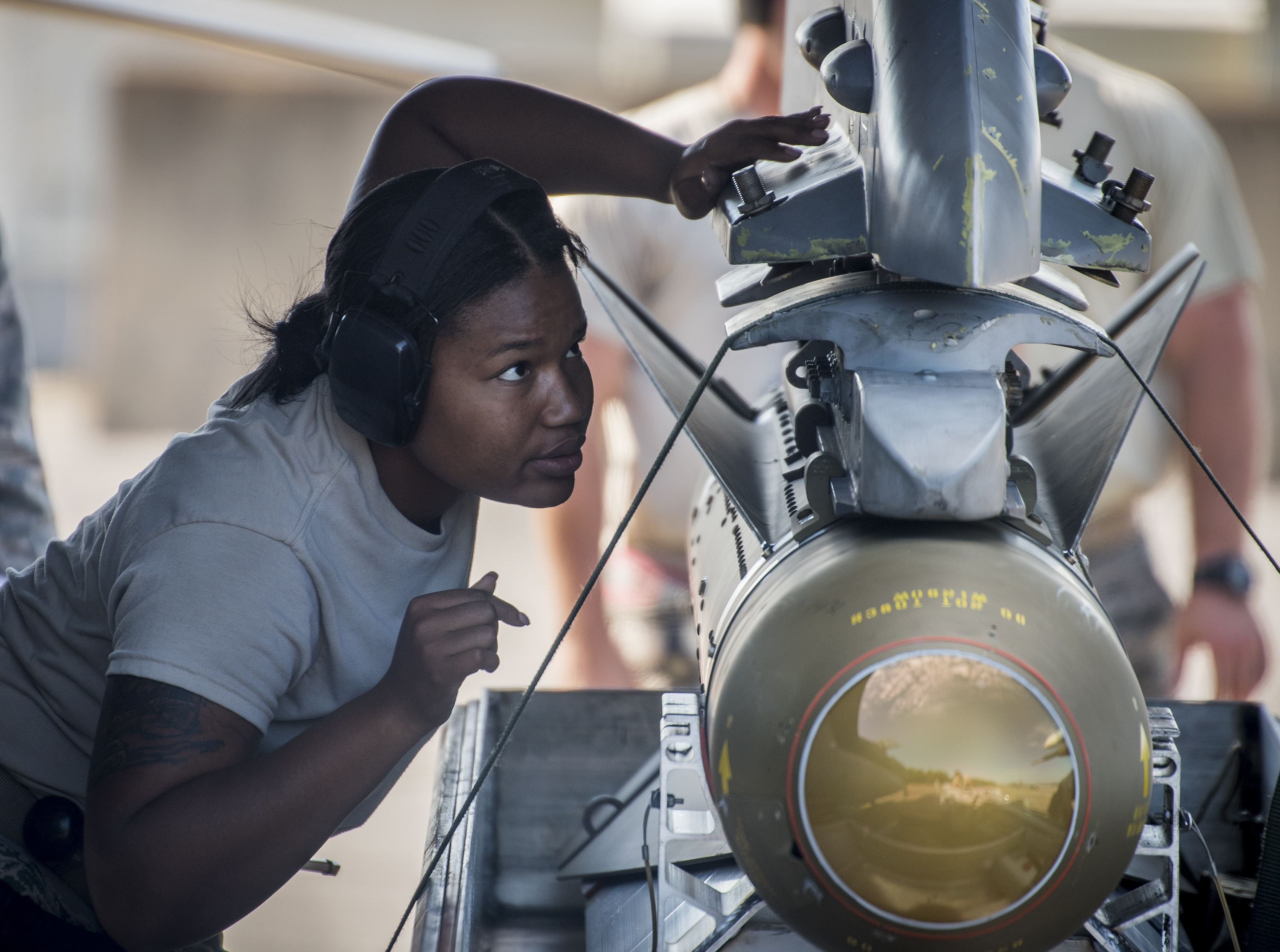 Air Force member inspects a bomb being mounted to a fighter jet.