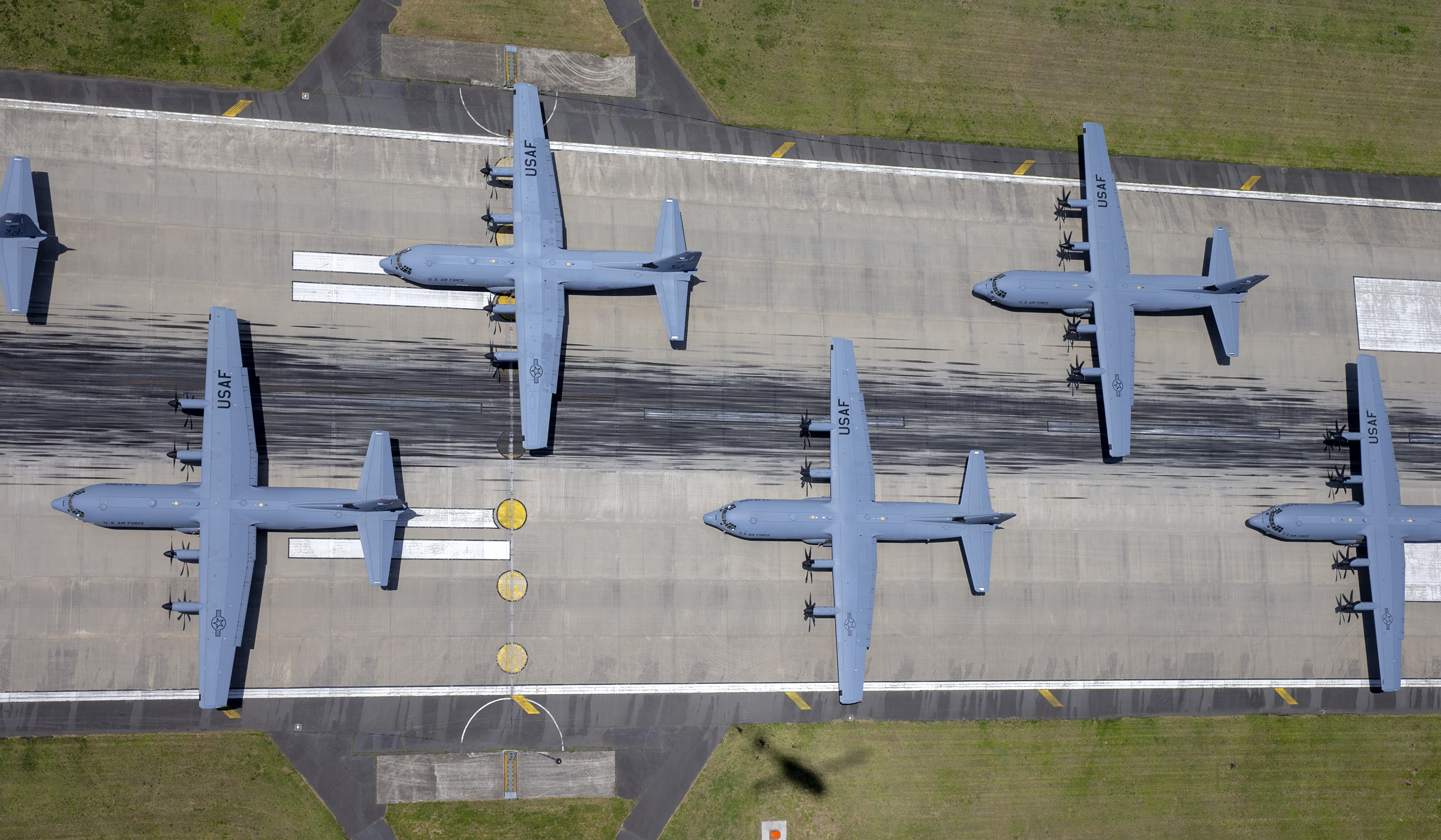 USAF cargo planes in formation on a runway.